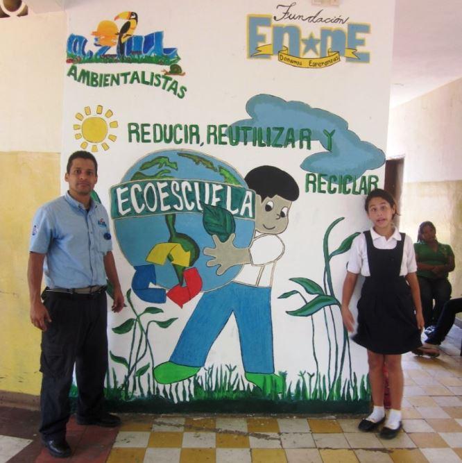 Gustavo Carrasquel, acompañado de una alumna de la escuela, mostrando el mural alegorico al Programa ECOescuela